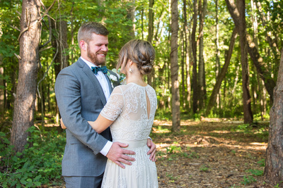 Bride and groom laughing in forest at Highland Brewing Wedding in Asheville