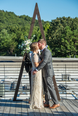 First kiss at wedding ceremony on rooftop at Highland Brewing Wedding in Asheville
