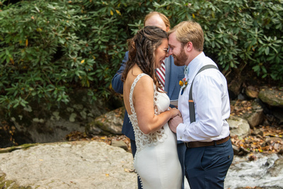 Bride and groom laugh after first kiss at Laughing Waters wedding venue near Asheville NC