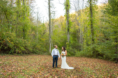 Bride and groom among fall leaves at Laughing Waters wedding venue near Asheville NC