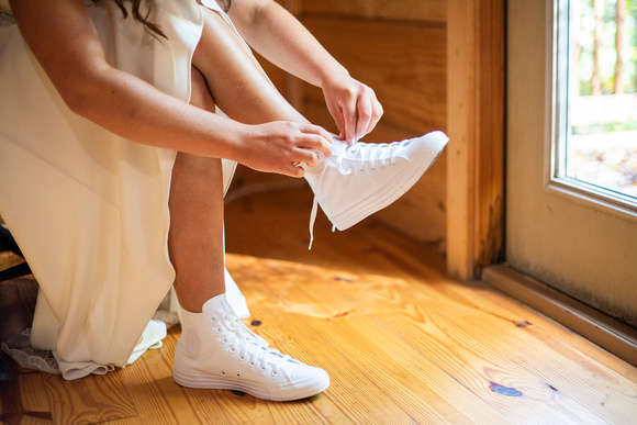 Bride putting on Converse wedding shoes at Laughing Waters wedding venue near Asheville NC