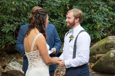 Couple holding hands during wedding ceremony in Hickory Creek at Laughing Waters wedding venue near Asheville NC