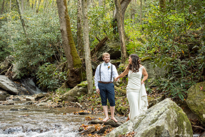 Couple standing in creek at Laughing Waters wedding venue near Asheville NC