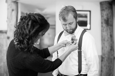 Groom pinning boutonniere at Laughing Waters wedding venue near Asheville NC