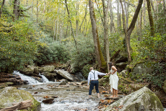 Groom leading bride through creek during fall at Laughing Waters wedding venue near Asheville NC
