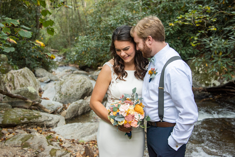 Groom talking to bride during photo at Laughing Waters wedding venue near Asheville NC