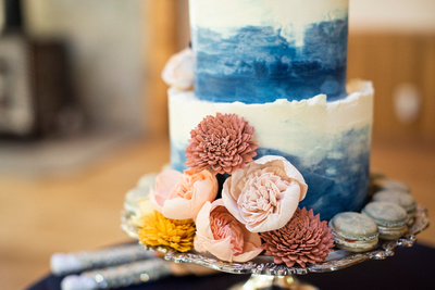 Wedding cake with wooden flowers and macrons by Layered by Lex at Laughing Waters wedding venue near Asheville NC