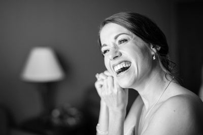 Bride laughing while getting ready for her wedding at The Lodge at Flat Rock