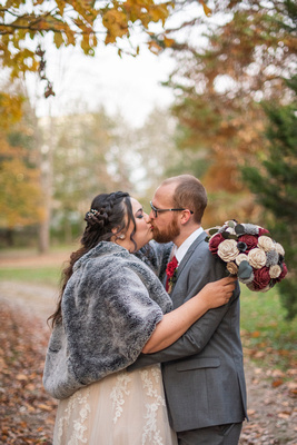 Bride and groom kissing during fall wedding at Asheville Botanical Gardens