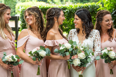 Bride and bridesmaids laughing at summer wedding at Hawkesdene in Andrews near Asheville
