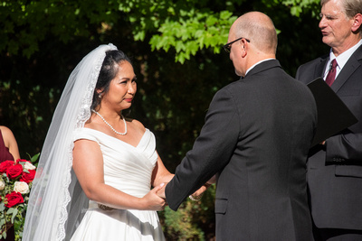 Bride holding grooms hands during ceremony at The Lodge at Flat Rock wedding