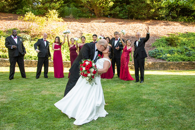 Groom dipping bride in front of wedding party near Asheville at The Lodge at Flat Rock