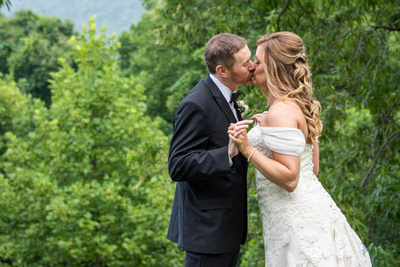 Bride and groom kiss during first look Engadine Inn Wedding in Asheville