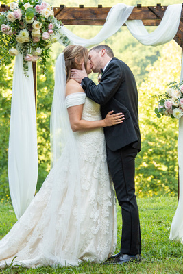 Bride and groom kissing at ceremony Engadine Inn Wedding in Asheville