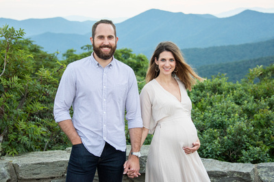 Man and woman holding hands in maternity photo at Craggy Pinnacle