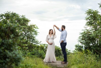 Man twirling pregnant woman at Craggy Pinnacle maternity session