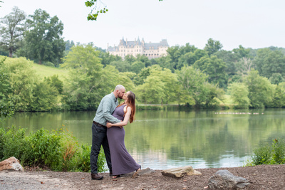 Biltmore house and lagoon with couple kissing at Biltmore Estate maternity photo session