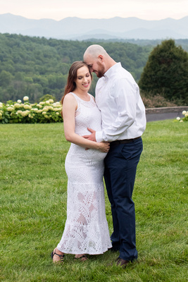 Couple touching foreheads in maternity photo at Biltmore Estate with mountain views