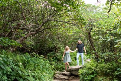 Bride leading groom down Craggy Pinnacle trail in summer