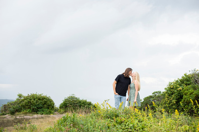 Couple kissing at summer engagement session at Craggy Pinnacle