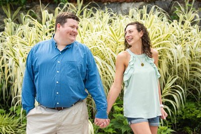 Engaged couple at Biltmore in walled garden holding hands in Asheville
