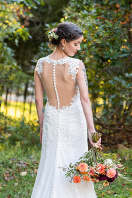 Bridal portrait showcasing back of lace dress at Brahma Ridge Event Center in Asheville