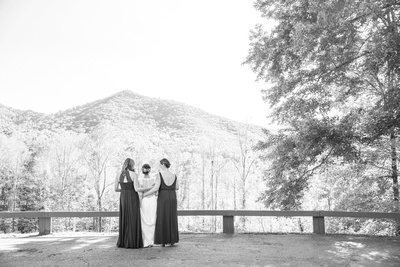 Bride and bridemaids looking out at mountains at Asheville wedding venue