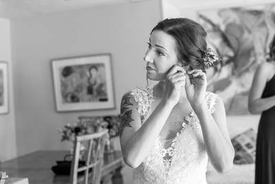 Bride putting on earrings at Brahma Ridge Event Center in Asheville