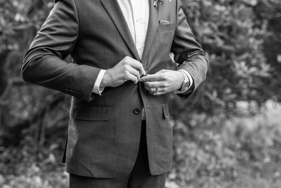 Groom buttoning jacket at wedding at Brahma Ridge Event Center in Asheville