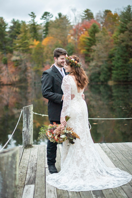 Bride and groom on dock at Highland Lake Inn during fall colors near Asheville