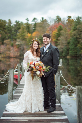 Bride and groom standing on dock at Highland Lake Inn wedding during fall