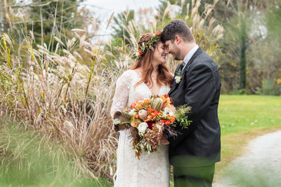 Bride and groom touching foreheads outside at Highland Lake Inn fall wedding