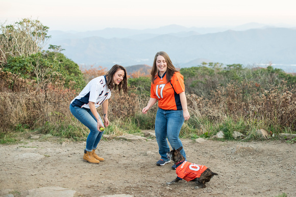 Same sex couple in Denver Broncos jersey at Craggy Gardens near Asheville playing with dog