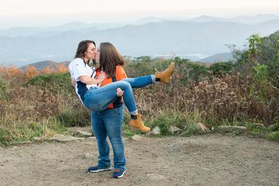 Same sex couple kissing with mountain views at Craggy Gardens near Asheville