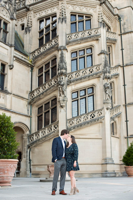 Couple kissing in front of grand staircase at Biltmore Estate in Asheville
