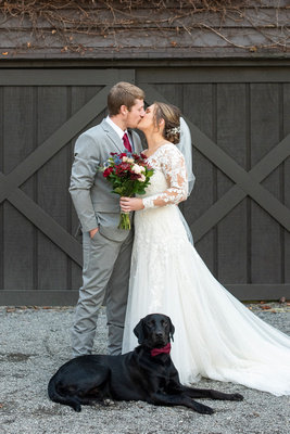 Bride and groom kiss while dog lays at their feet at Hawkesdene in Andrews NC