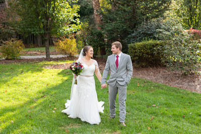 Bride and groom walk across grass during wedding at Hawkesdene in Andrews NC