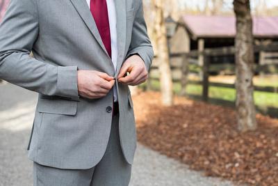 Groom buttoning jacket at Hawkesdene in Andrews NC wedding