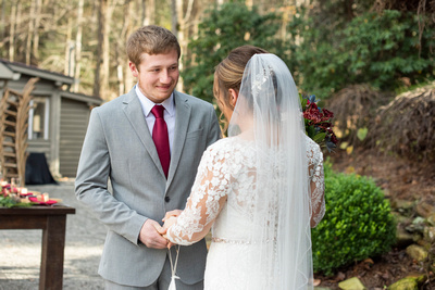 Groom looks at bride during first look at Hawkesdene in Andrews NC
