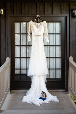 Long sleeve wedding dress and blue wedding shoes hanging in doorway at Hawkesdene in Andrews NC
