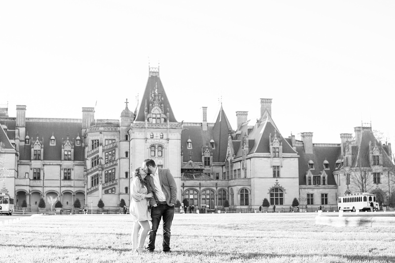 Couple kisses in front of Biltmore house at Biltmore Estate in Asheville during engagement photos