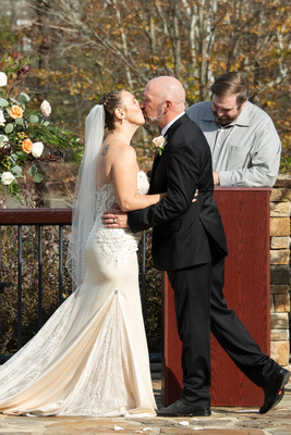 Bride and groom kiss at wedding ceremony at Stone River in Columbia SC
