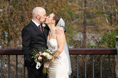 Bride and groom kiss during photos at Stone River in Columbia SC