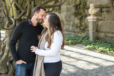 Couple touching noses at Biltmore Estate in Asheville under pergola