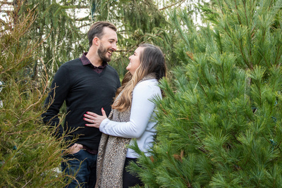 Engaged couple between Christmas trees at Biltmore Estate in Asheville