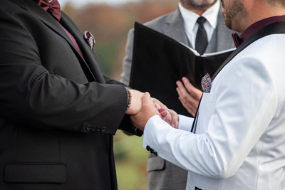 two men holding hands during wedding ceremony near Asheville, NC
