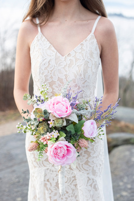 Bride holding wedding bouquet at Jump Off Rock hear Hendersonville in long lace dress