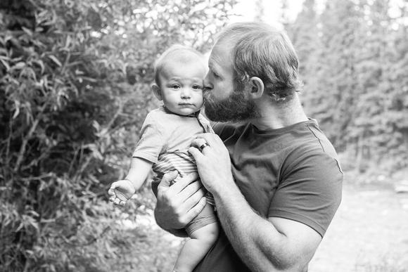 Dad kissing baby at Gallatin River near Big Sky, MT