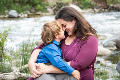 Mom and son snuggling along shore of Gardner River in Yellowstone National Park by Asheville family photographer